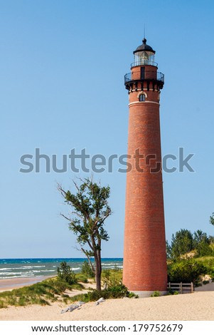 The Little Sable Point Lighthouse stands on a sandy beach of Michigan's Lake Michigan coast in Silver Lake State Park. - stock photo