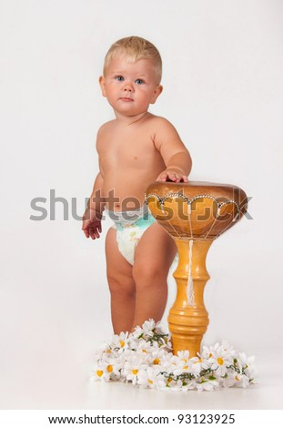 The little white boy stands with an African drum. - stock photo