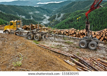 The loader is used to lift the log truck trailer from the truck and line up with the truck hitch.  - stock photo