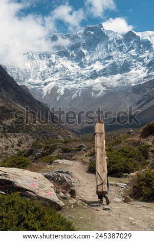 The locals delivers construction materials to the upper vilage on a  Annapurna Circuit - most popular turists trek in Himalayan mountain massive in Nepal.