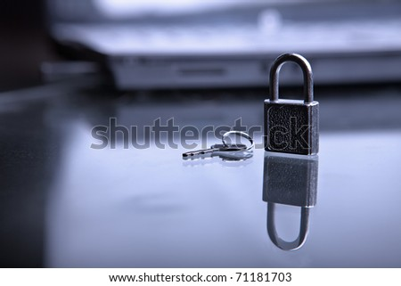 The lock with a key against the laptop - stock photo