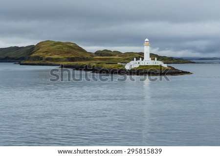 The lone white lighthouse of Lismore between a gray silver sea and sky, near Mull and Oban, in the Inner Hebrides of Scotland. This beacon confers guidance, warning and safety to ships near the coast. - stock photo