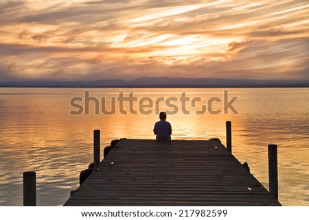 the lonely boy at sea - stock photo