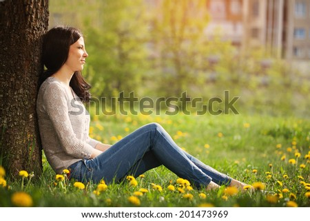 The lonely girl sits at a tree looks in a distance