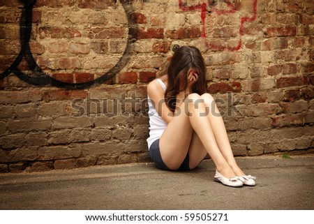 The lonely girl sits at a wall - stock photo