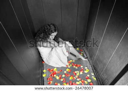 The lonely girl sits on a lift floor - stock photo