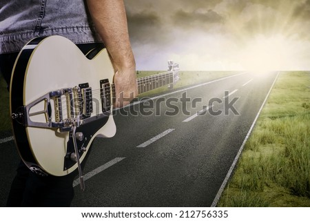 The lonely guitarist walking on road, shot outdoors at dusk - stock photo
