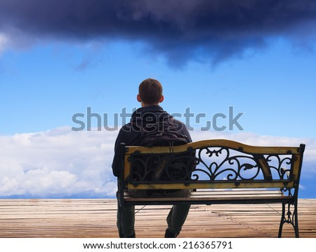 The lonely man sits on a decline. Creative Outdoor Photo. - stock photo