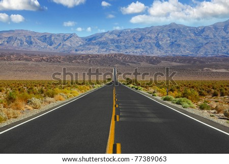 The lonely red car on the road, crossing enormous Death the Valley in California. - stock photo