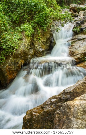 The long exposure image of a beautiful waterfall in the forest - stock photo