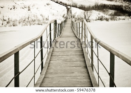 The long foot rural bridge through a backwater covered with shows. - stock photo