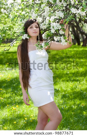 The long-haired girl against blossoming apple-trees