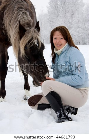 The long-haired girl and her horse. - stock photo