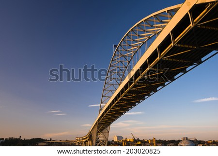 The longest in Europe and America arched Fremont Bridge Portland Oregon Willamette River. Painted metal truss road bridge view from below against the blue sky and the coastal industrial area. - stock photo