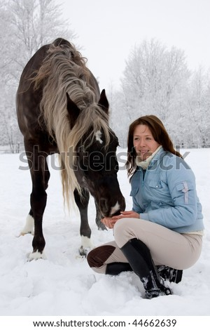 The longhaired girl and her horse. - stock photo