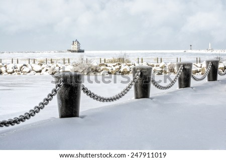 The Lorain Lighthouse is a historic landmark on the shores of Lake Erie, one of the Great Lakes. Seen here in winter with snow and ice.  - stock photo