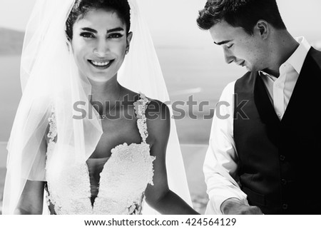 The lovely couple in love hold hands near sea - stock photo