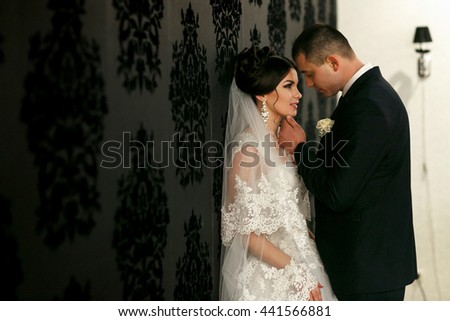 The lovely couple in love stand near wall - stock photo