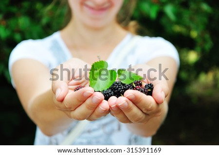 The lovely girl offers ripe berries of a mulberry. The girl holds berries in hand. - stock photo