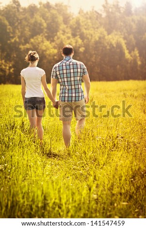 The loving couple walks in the field - stock photo