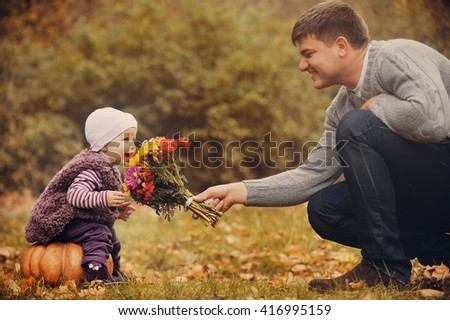 the loving father gives a color bouquet in the color to the little daughter in autumn park