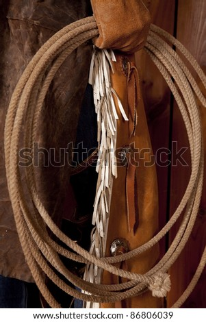 The lower half of a cowboys body holding on to a rope. - stock photo
