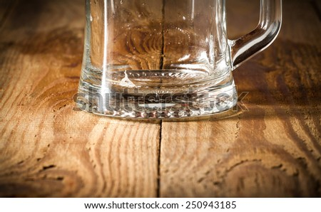 The lower part of the empty beer glass on a wooden table - stock photo