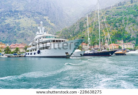 The luxury yachts in port of Kotor wait for the better weather, Montenegro. - stock photo