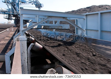 The machine belt is transporting and moving the mass of lignite to the tower plant t for produces the electricity - stock photo