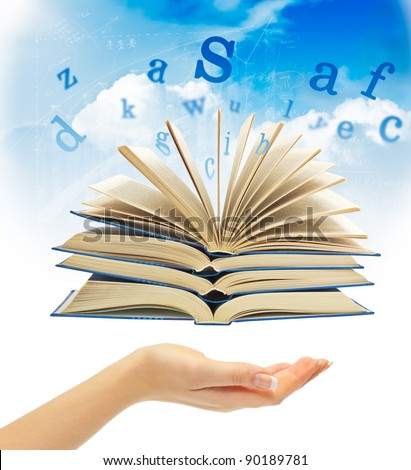 The Magic Book and the letters over hand on a sky background. Education concept - stock photo