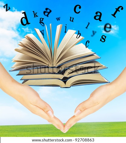 The Magic Book and the letters over hands on a sky background. Education concept