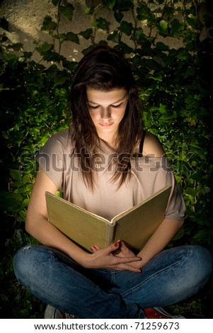 The magic of books. Beautiful young brunette immersed in reading a book, portrait with creative lighting.