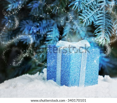 The magic of Christmas night gift in the snow under the tree Christmas - stock photo
