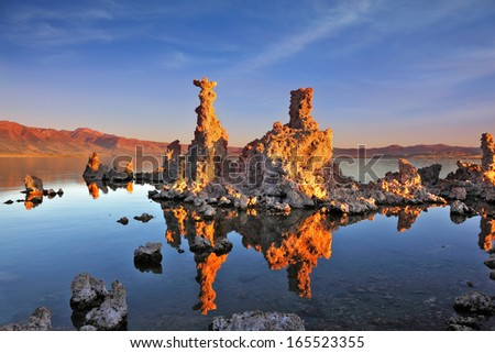 The magic of Mono Lake. Outliers - bizarre calcareous tufa formation on the smooth water of the lake. Orange sunset - stock photo