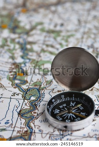 The magnetic compass is located on a topographic map. Satellites adventure - map and compass. - stock photo
