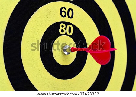 the magnetic needle darts in the center of the target in the background - stock photo