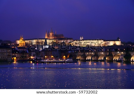 The magnificent Prague Castle at night along the River Vltava with Charles Bridge - stock photo