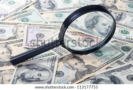 The magnifying glass lying on banknotes close-up - stock photo