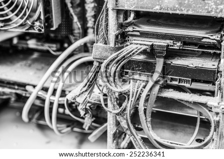 The main components of the outdated, dusty and non-working computer, supply and data cables. In black and white tones - stock photo
