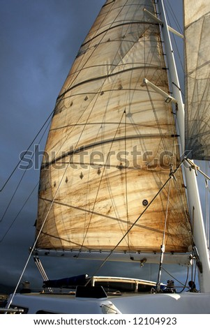 The main sail on a catamaran, lit by early morning sunlight. - stock photo