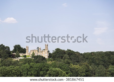 The majestic old German castle on the hill in a summer forest. The castle is located in Dresden, Germany. - stock photo