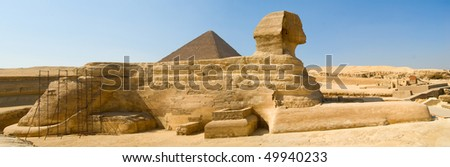 The majestic Sphinx on the background of the famous pyramids - stock photo
