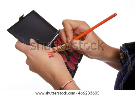 the make-up artist Caucasian girl holding a makeup brush in hand in a denim overalls on a white background