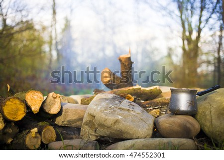 The maker stands near a bonfire in a clearing for camping.