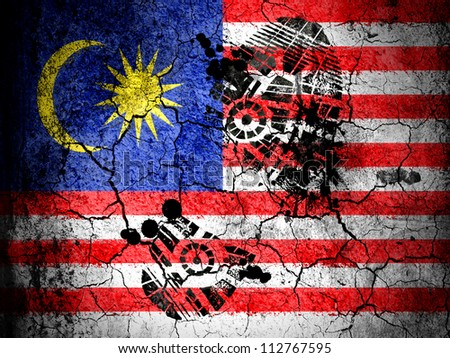 The Malaysia flag painted on  cracked ground with vignette with dirty oil footprint over it