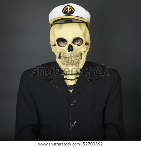 The man - a skeleton in a naval cap on a dark background - stock photo