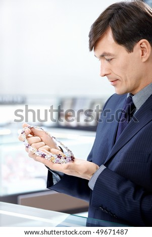 The man aged considers a jeweller necklace - stock photo