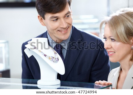The man and the woman choose a gift in jeweller shop - stock photo