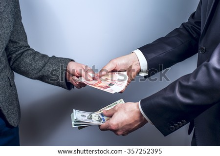 The man and the woman exchange US dollars and Russian rubles on grey background. Horizontal view.