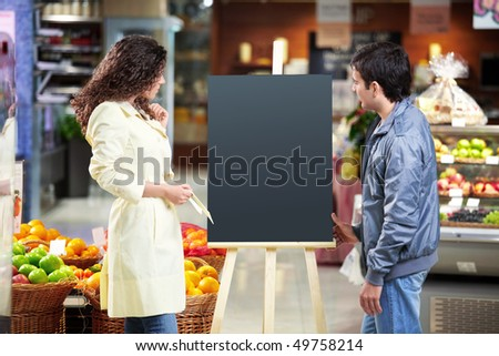 The man and the woman look at an empty board in shop - stock photo